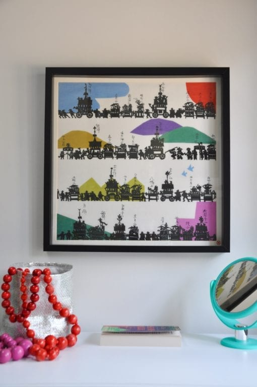 A colourful framed Japanese silkscreen above a dressing table.