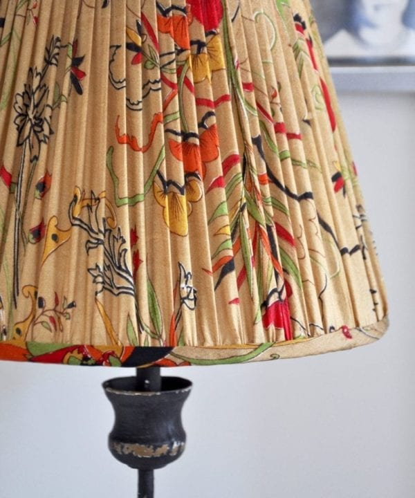 An Indian lampshade, handmade from vintage Indian saree silk in warm gold, red, green and yellow.