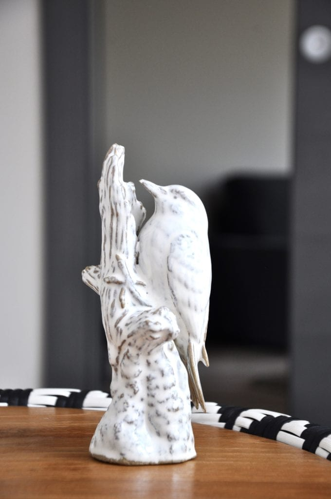 White ceramic bird sculpture on a black, white and wood woven table.