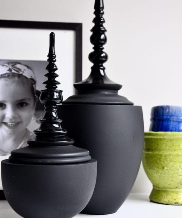 Matt and gloss black decorative lidded pots in two sizes.