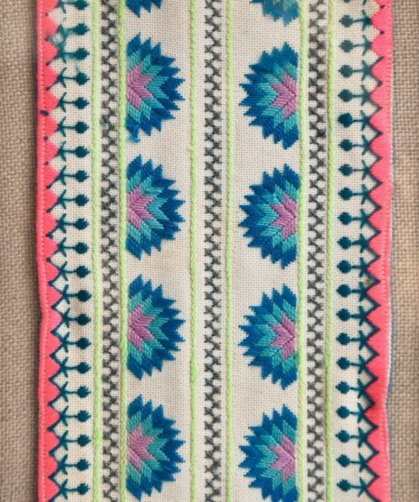 A framed Thai hill tribe textile hand-embroidery in coral and blue.