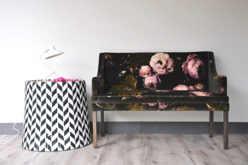 A velvet-upholstered floral bench next to a woven black and white drum side table with modern white metal lamp.