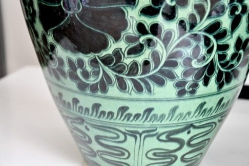 Detail of an Asian pottery green pot, hand-decorated with Lotus flowers.