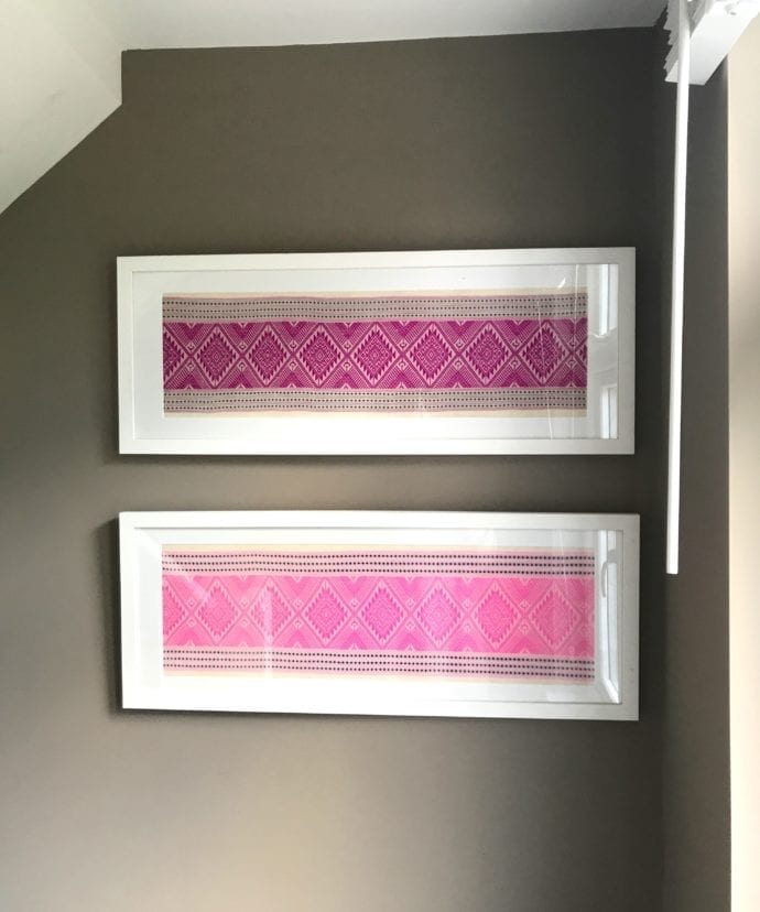 A pair of candy and magenta pink white wood framed textiles hung on a taupe wall by a window.