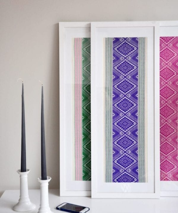 Vibrantly-hued framed textile art, showcasing purple, pink and green Thai cotton wovens framed in tall, white-washed wooden box frames styled on a white table with a pair of candlesticks.