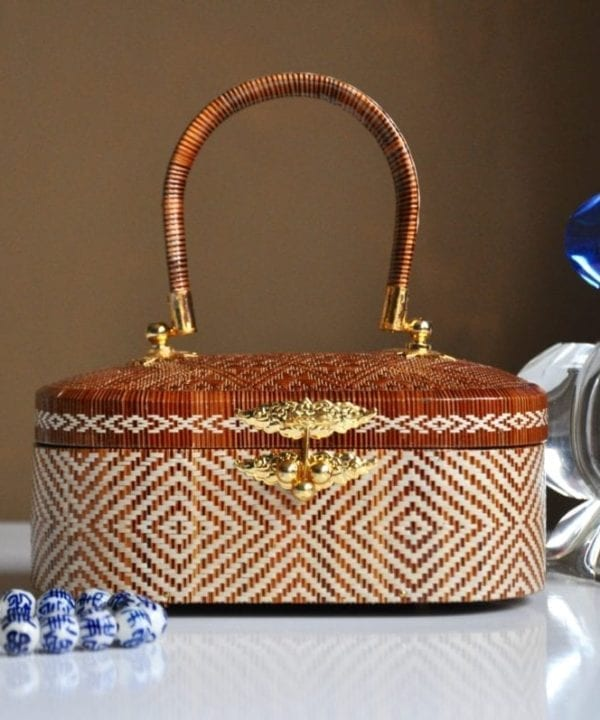 A delicately handmade Thai small woven bag or trinket box displayed on a dressing table.