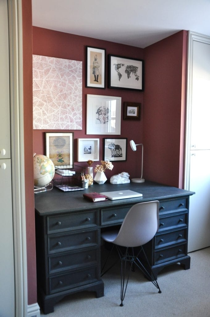 A smart, study area niche with a black-painted desk flanked by built-in cupboards either side.