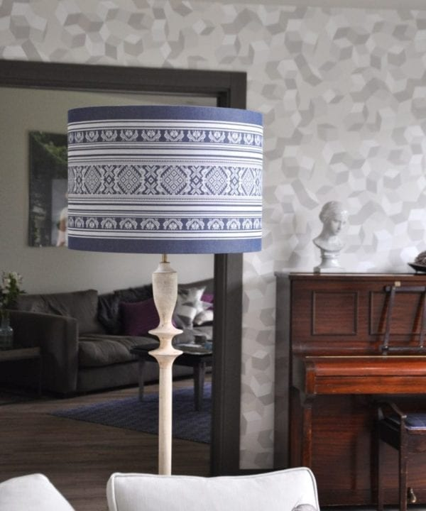 A large blue and white lampshade with a Folk style design inspired by traditional Hungarian costume.