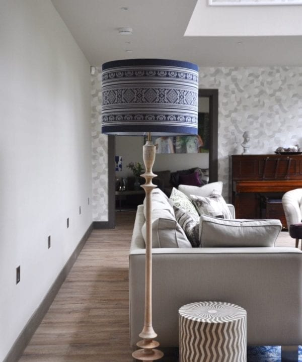 A tall white-washed turned wood floor lamp with patterned blue drum shade at the end of a boxy, modern sofa in a modern, double-height space.