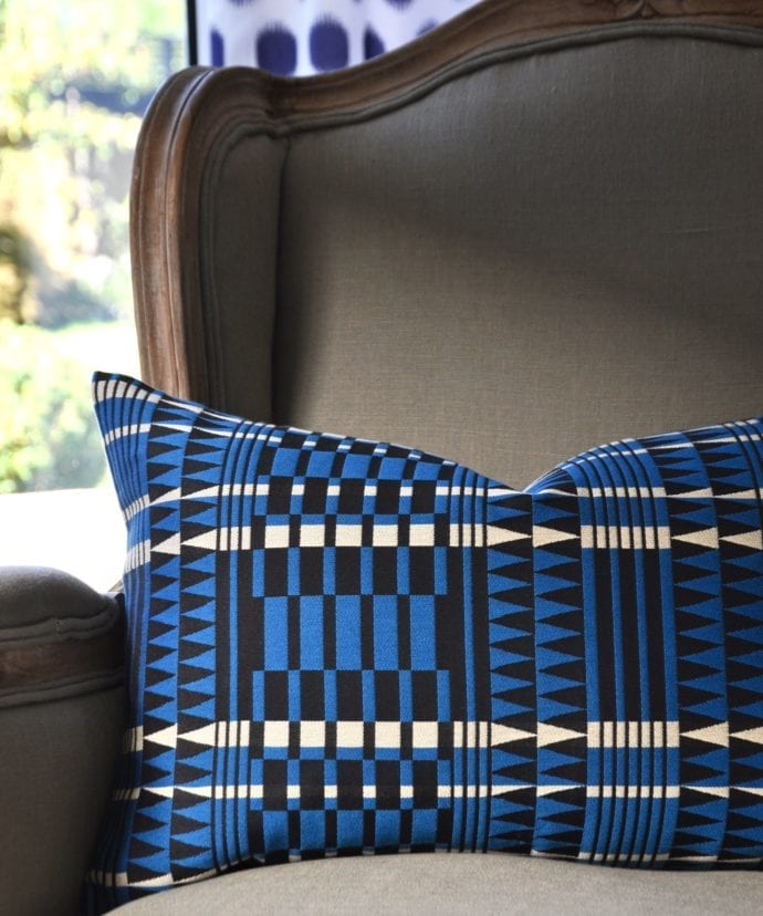 A sky blue, black and white African geometric or tribal style cushion on a French armchair.