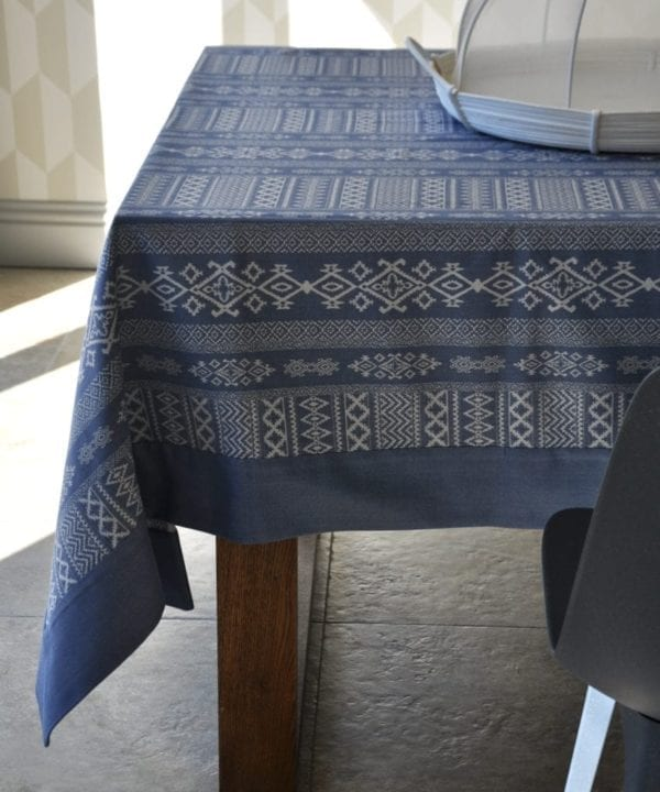 Luxury blue linen tablecloth with Arabian architectural motifs in the weave, shown on a modern, wooden dining table.