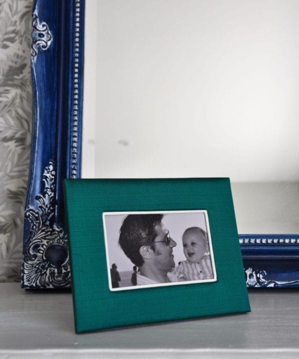 A Thai-silk, emerald green photograph frame with a picture of a parent and baby, against a blue mirror backdrop.