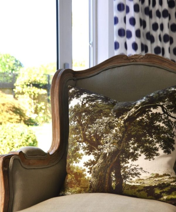 Tree cushion in moss green on a French bergere armchair with a view to outdoors.