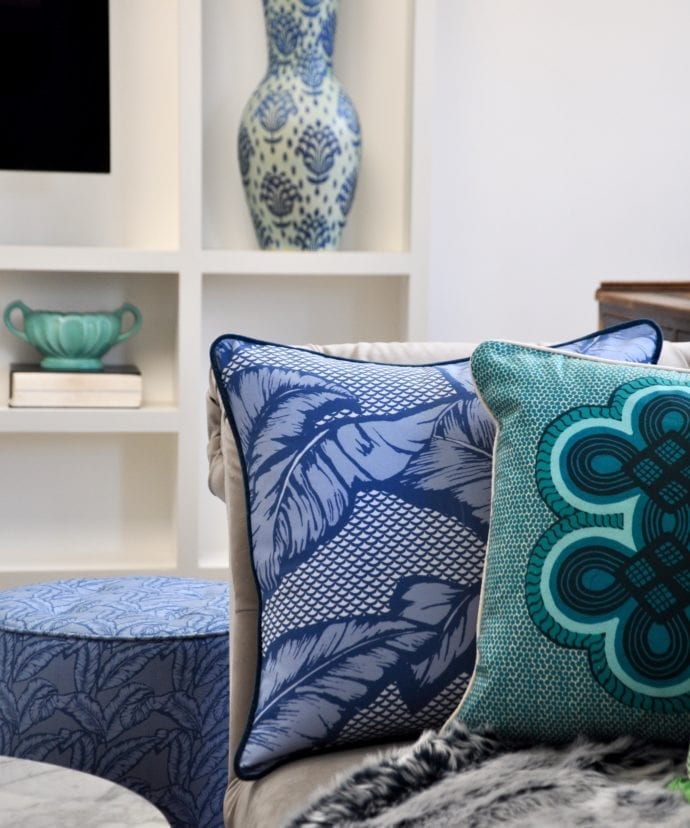 African motif cushion in blue and aqua on a cosy sofa with a faux fur throw and ceramic pots on shelves in the background.