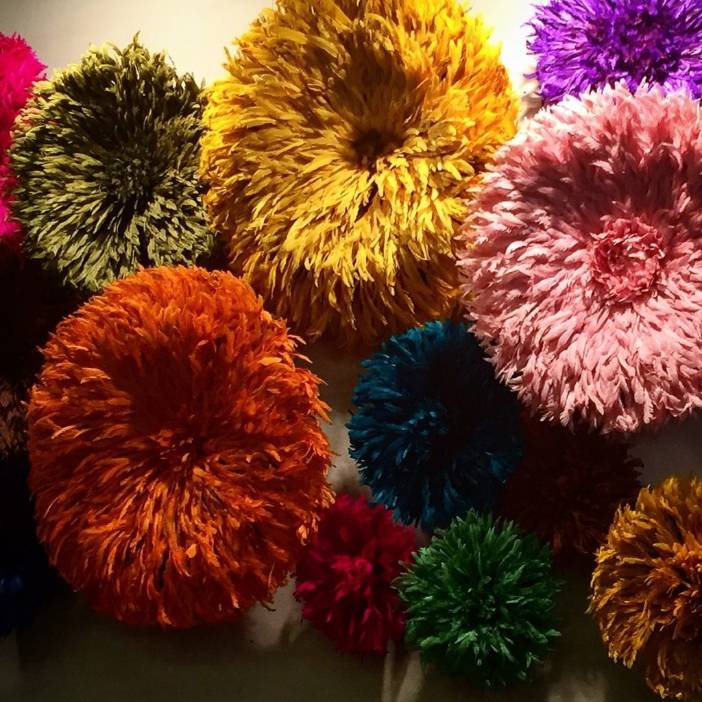 A wall display of colourful. African. tribal Juju hats made from feathers.