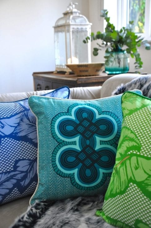 Brightly coloured African style cushions on a sofa.