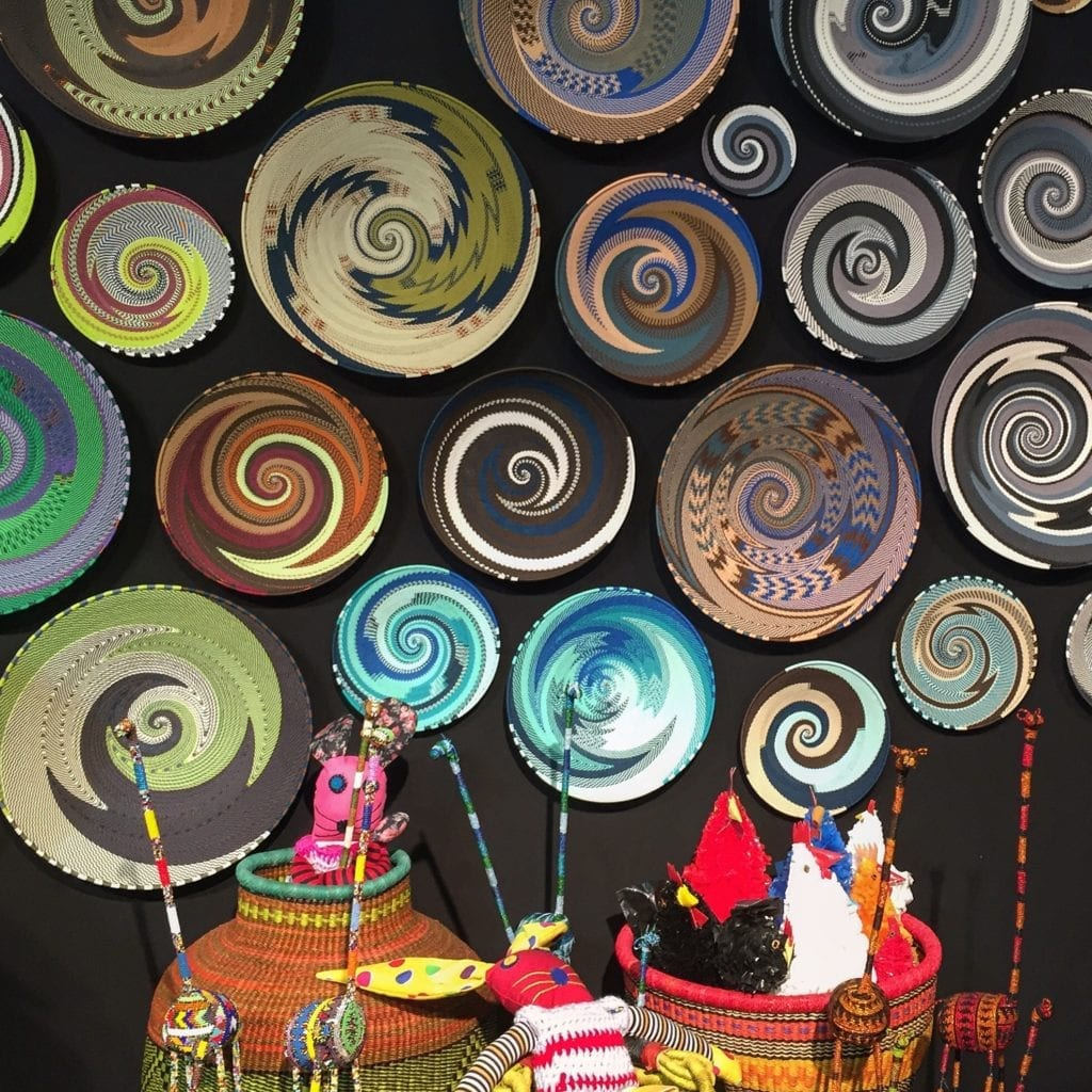 A wall display of colourful African, telephone wire baskets.