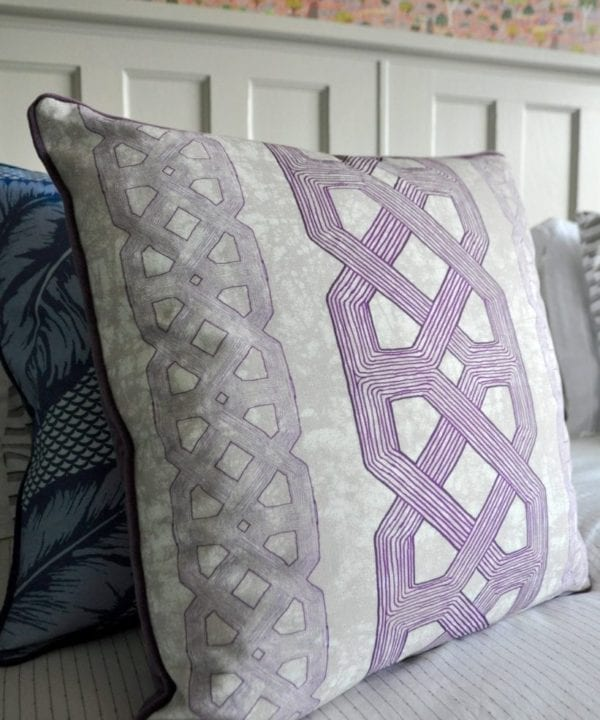 Purple lattice print African tribal cushion on a bed.