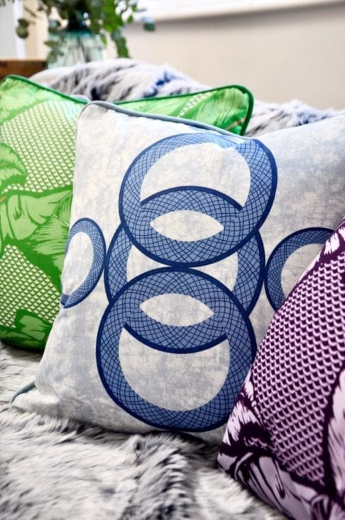 A close up shot of an African circles print cushion in blue with other brightly coloured cushions on a cosy winter sofa.
