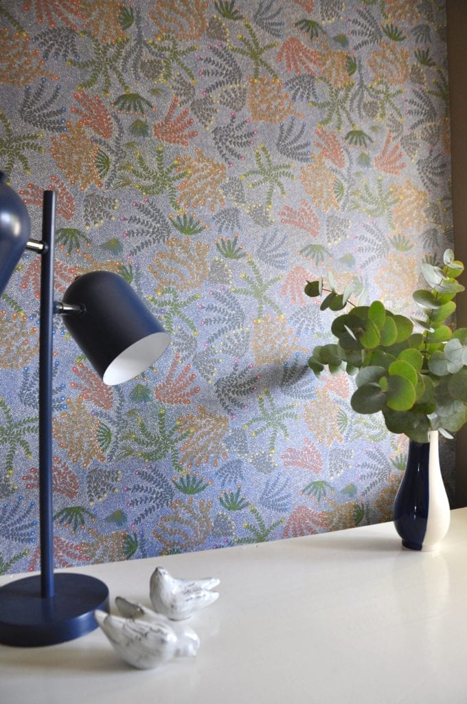 A blue angle poise lamp in foreground with blue floral Aboriginal symbols wallpaper.