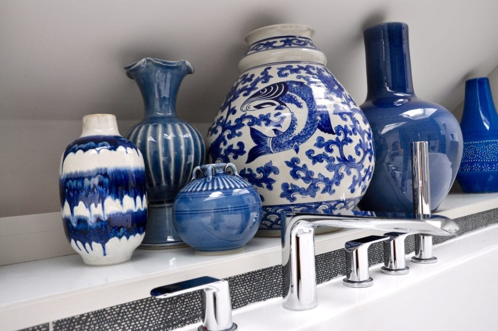 A collection of blue and white Asian vases behind a modern bath tub and taps.