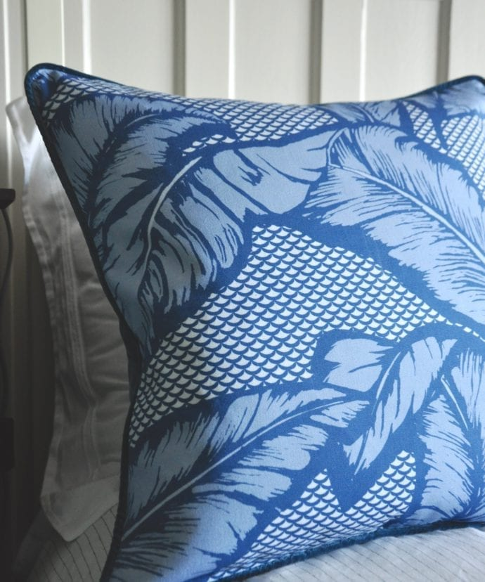 A blue tropical banana leaf print cushion on a bed.
