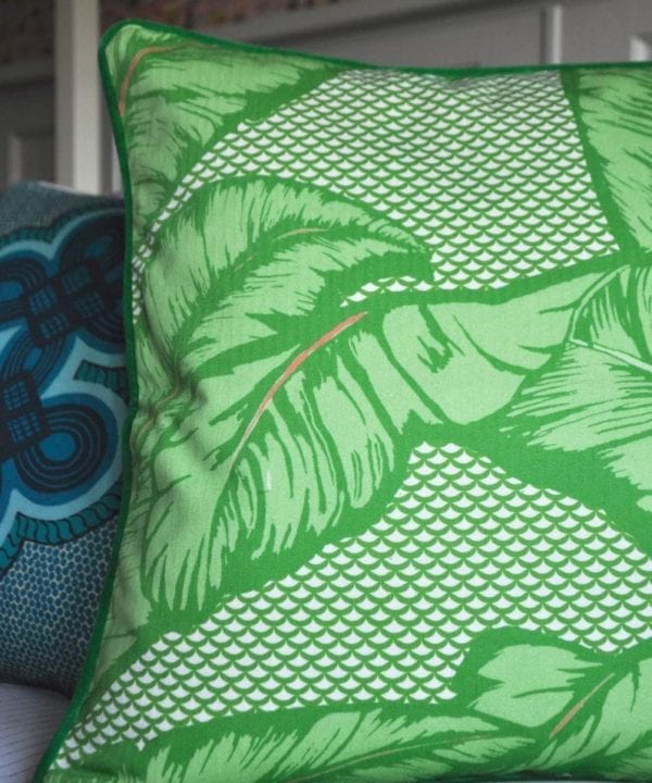 A bright green tropical banana leaf print cushion on a bed.