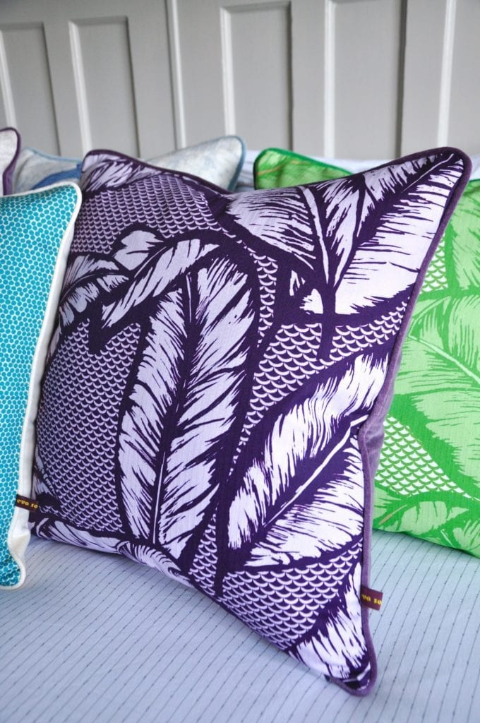 A deep purple Banana leaf print cushion with purple velvet back on a bed with other colourful cushions.