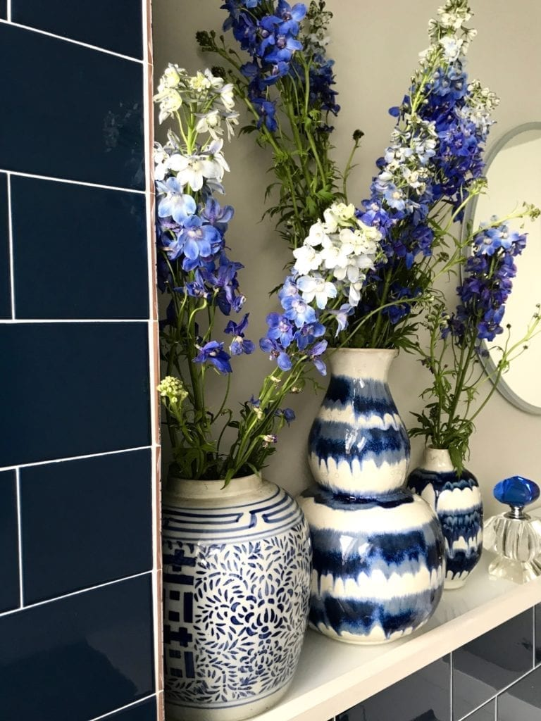A display of delphiniums in a selection of Asian blue and white china vases in a blue, tiled bathroom.