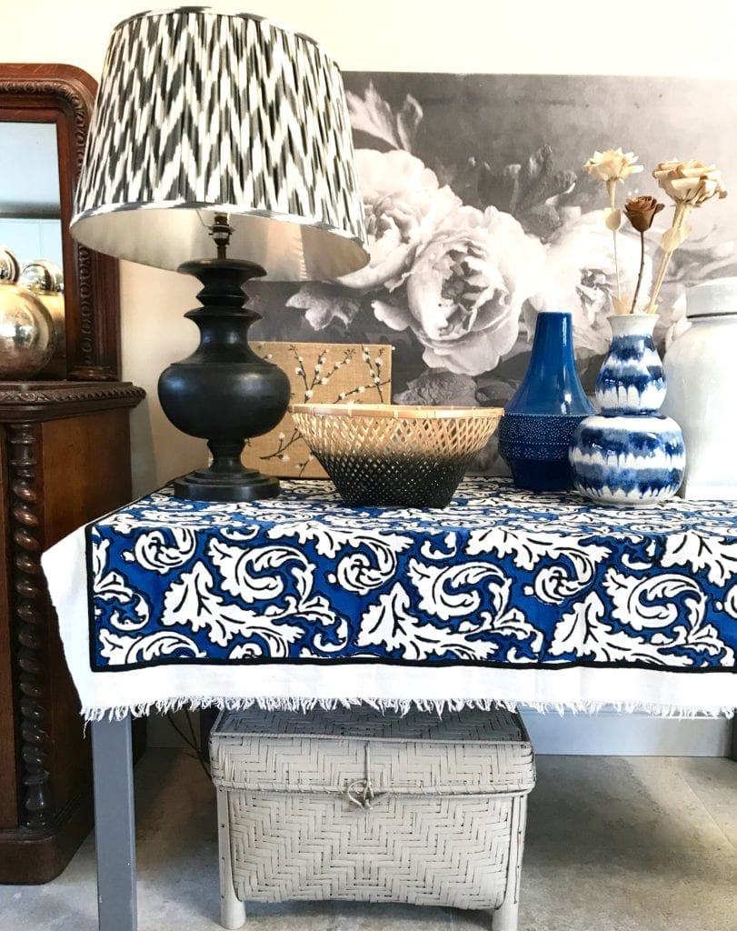 A monochrome and blue sideboard still life display showcasing a large scale Ikat lamp shade with turned wood base, baskets, ceramics and botanical textiles and a large floral canvas of Peony in black and white.