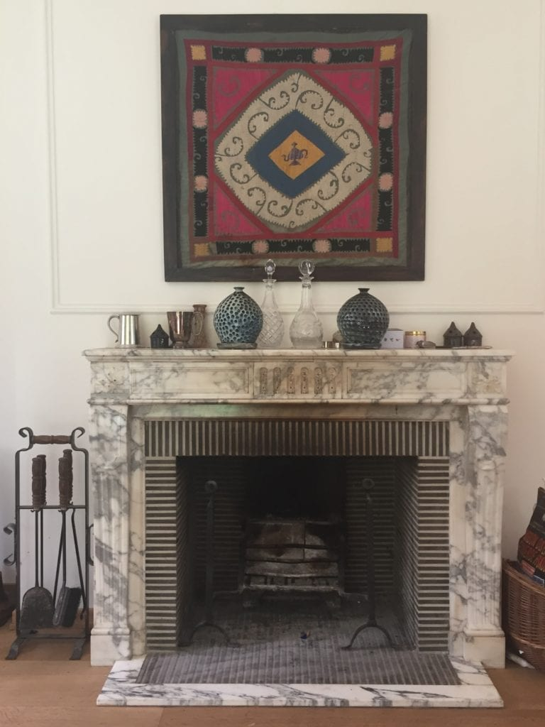 A marble fireplace with a framed central European textile displayed above it.