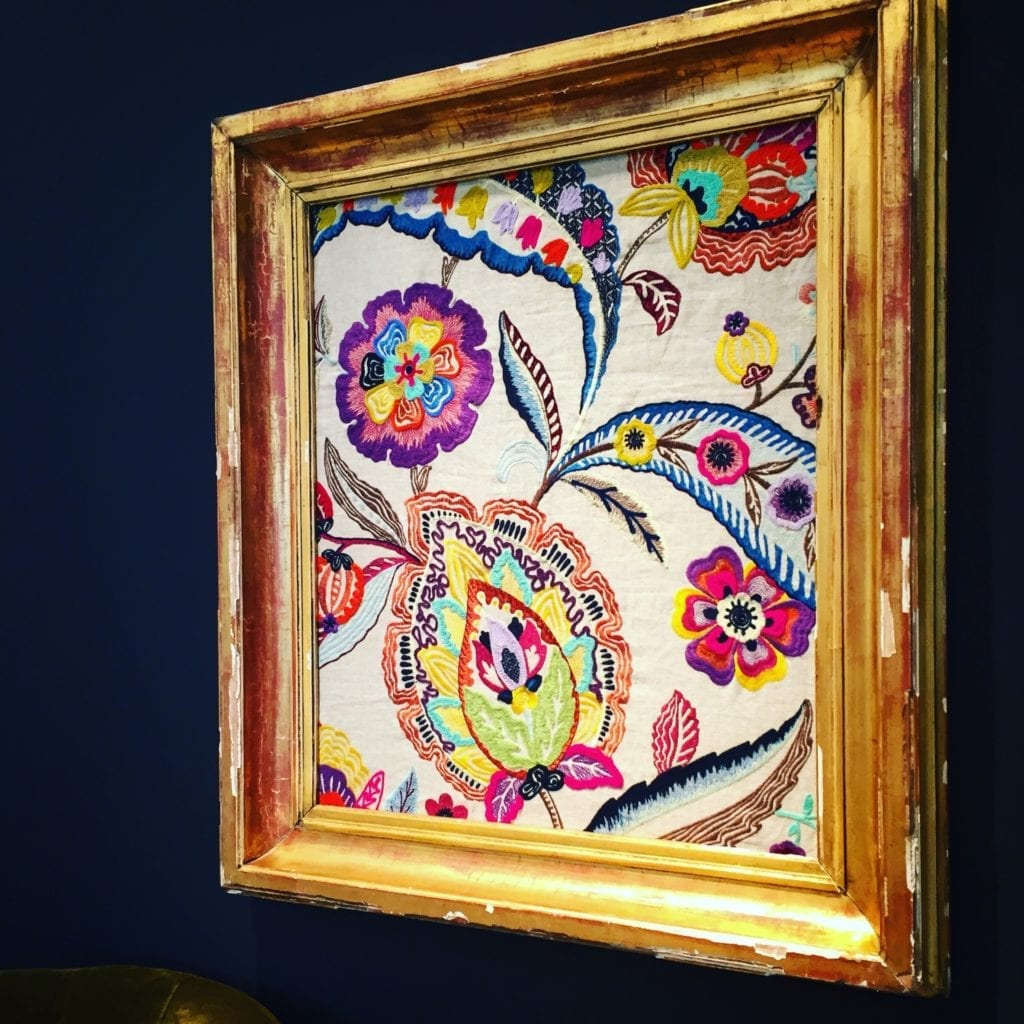 Colourful embroidered textile in a vintage frame.