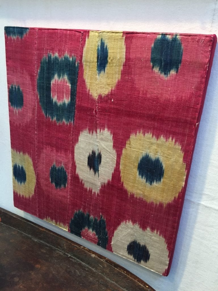 A vintage silk ikat textile stretched on a canvas for display.