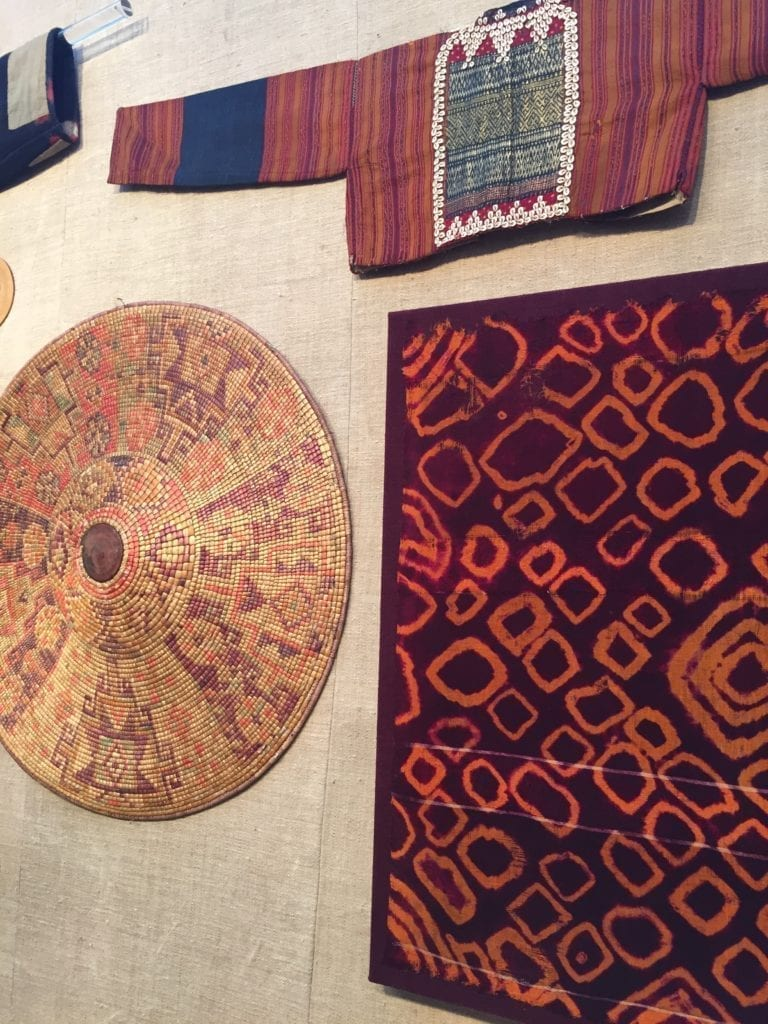 Cultural textiles and artefacts displayed on a wall.