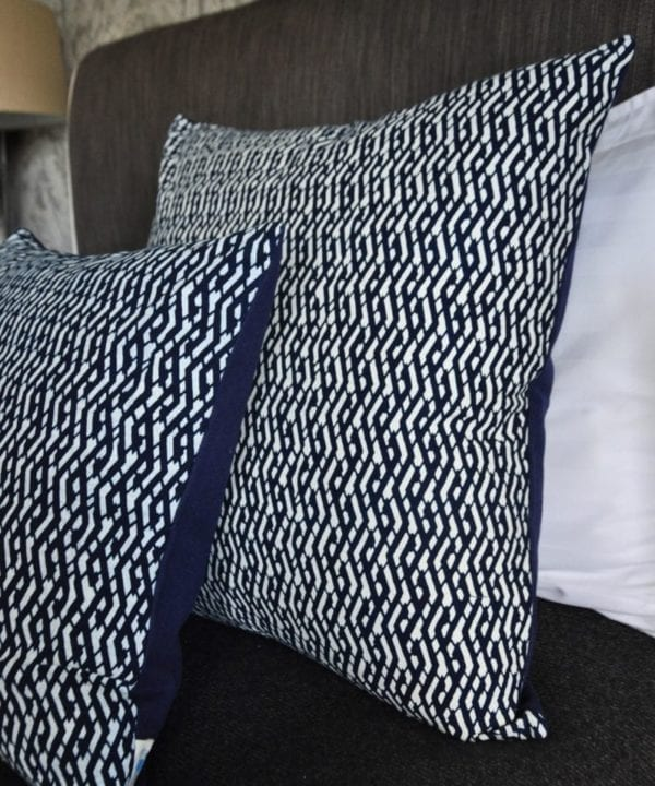 Indigo cushions with Eastern styling dressing a bed.