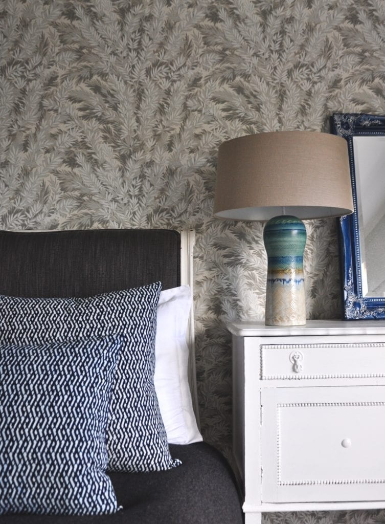 Asian lattice print cushions in indigo blue dressing a bed, a pottery lamp with linen shade and yew print botanical wallpaper.