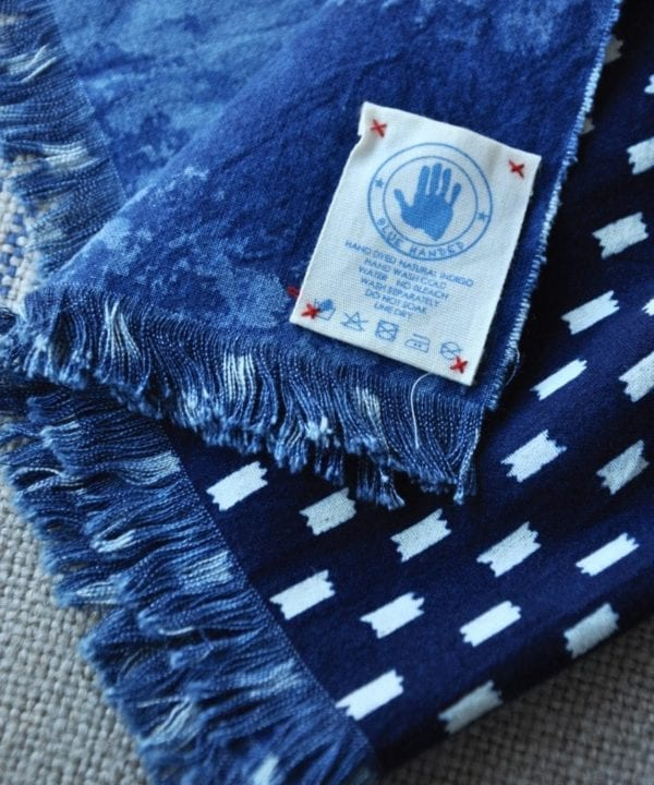 Shot of an indigo blue check scarf showing the Blue Handed label.