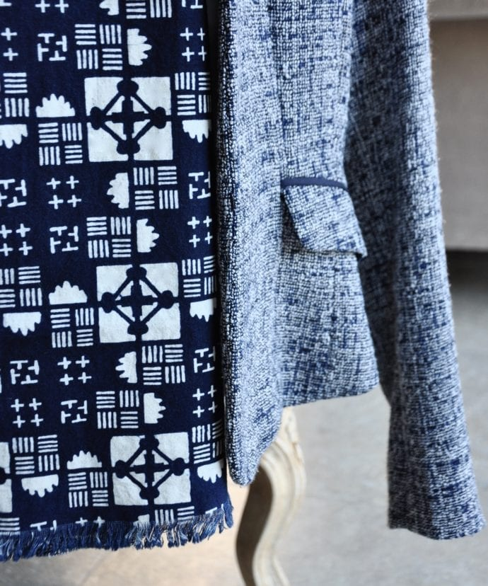 Close-up of a geometric print scarf hung on a ladies blue tweed jacket on a chair.