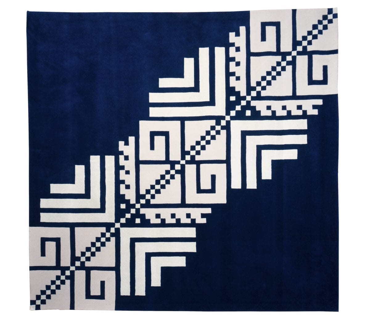 Overhead shot of a Romanian folk pattern rug in navy and white.