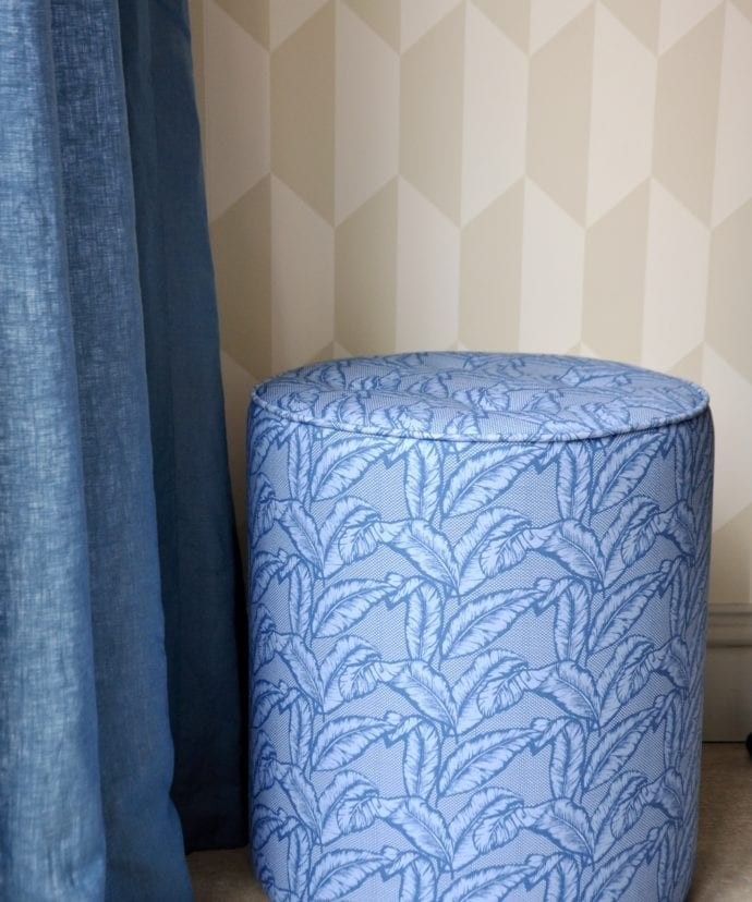 A blue banana print pouffe against neutral geometric wallpaper and next to a linen curtain.