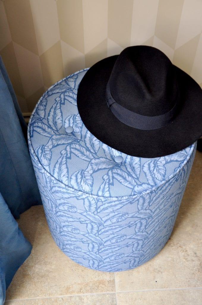 A blue banana leaf print pouffe with a navy, felt Trilby hat on top.