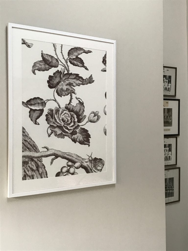 Framed section of floral rose wallpaper in chocolate brown.