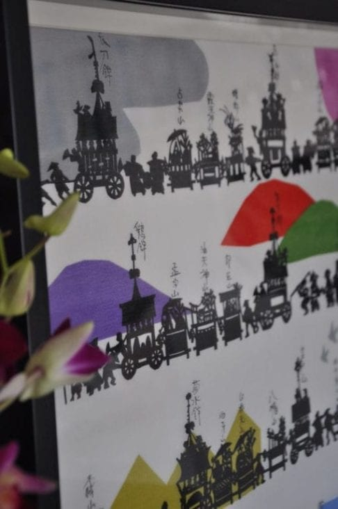 A black framed, colourful, Japanese, silkscreen print with pink orchids just visible in the foreground.