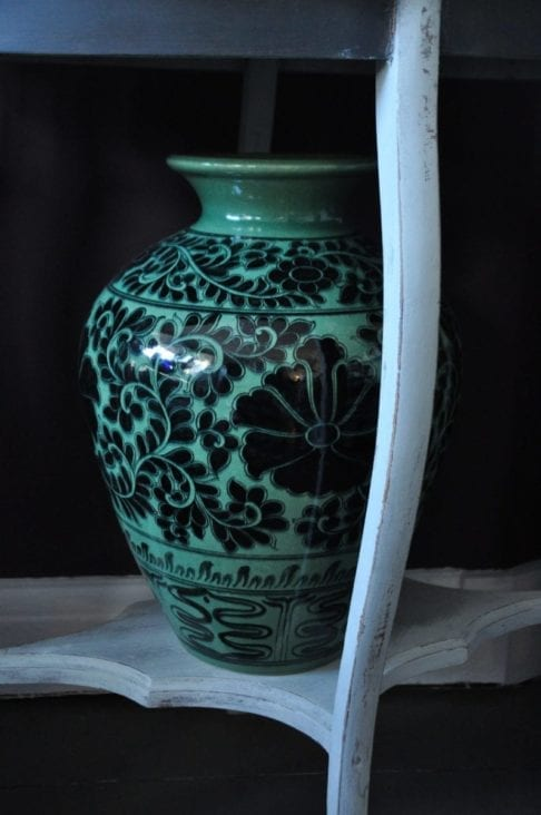 A large, patterned urn-shaped pot in deep green colour with black Thai cultural motifs and a Lotus flower design.