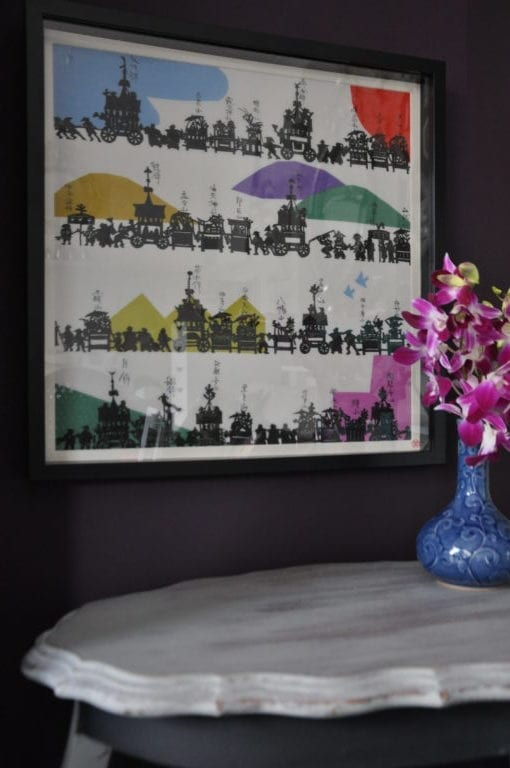 A black framed, colourful, Japanese, silkscreen print above A French side table with a vase of pink orchids.