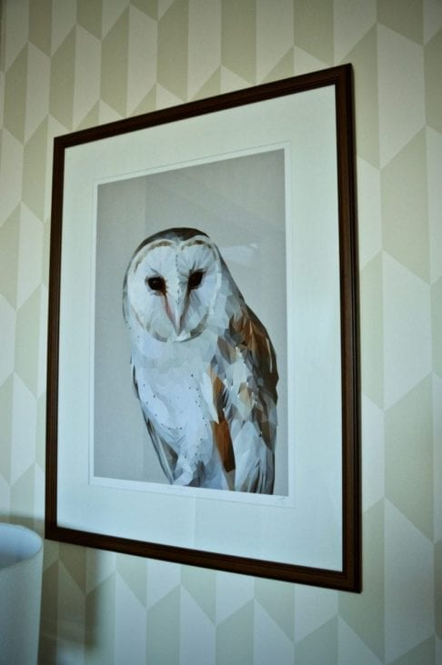 A giclée print of a barn owl with mahogany frame against neutral geometric wallpaper.
