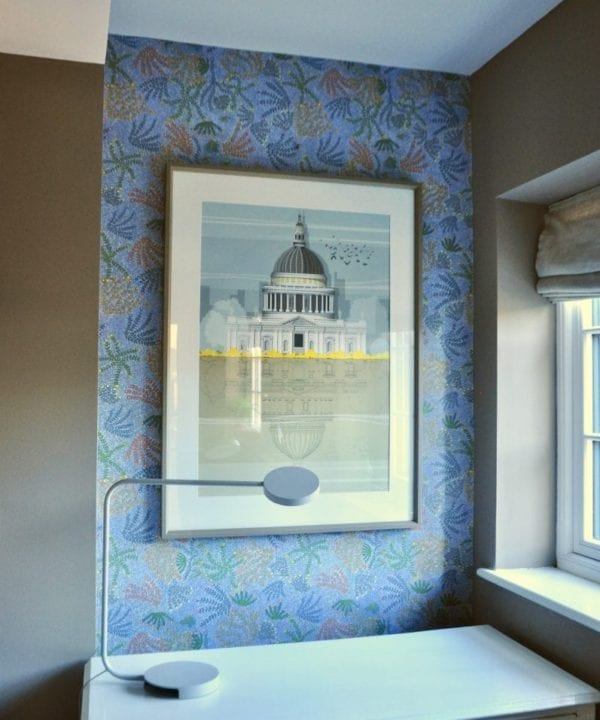 A framed large print of St.Paul's cathedral against blue floral wallpaper with a white sideboard and modern table lamp in the foreground.