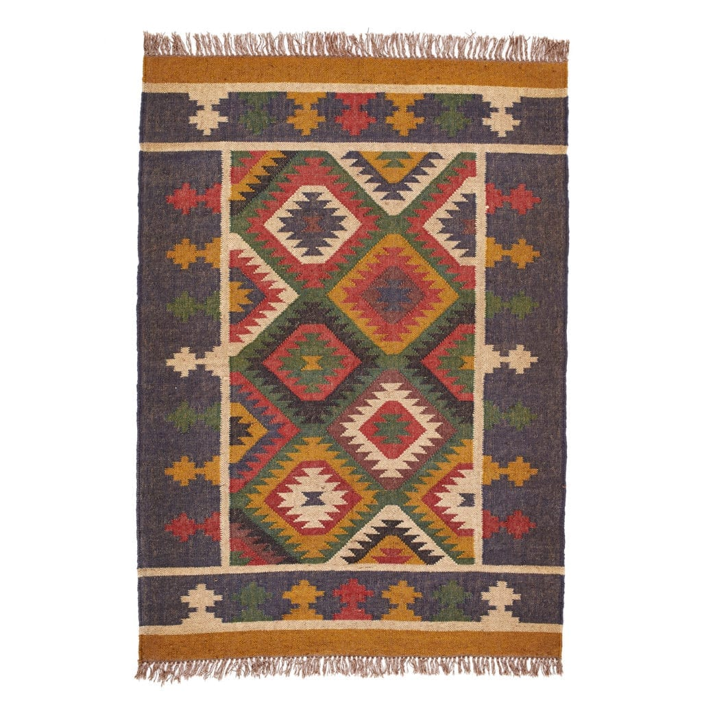 An Aztec-inspired rug with diamond pattern in mustard and brick red with tasselled ends.