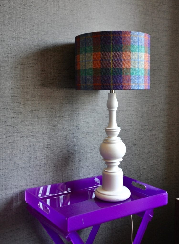 A purple, orange and blue check drum shade made from Harris Tweed on a white wooden lamp base on a purple perspex table. The lampshade is availble to order through Telescope Style.