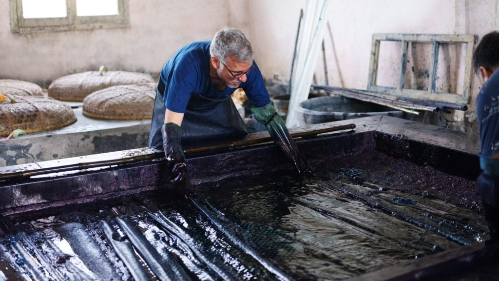 John Abbate gets truly 'blue handed' while dipping the cloth in the indigo vat.